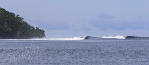 A remote left grinds down the reef in the Banyaks